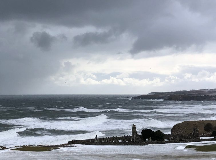 View of St Mary of the Storms graveyard taken from slopes of golf course, looking beyond to stormy rolling waves