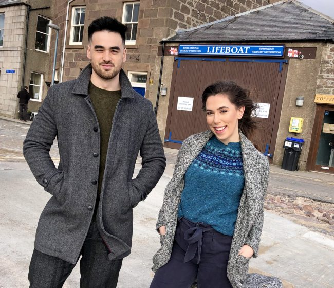Attractive couple on harbour slipway, girl wearing lovely woollen jersey