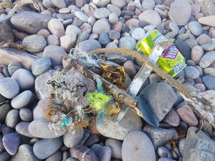 Assortment of litter on beach - can, plastic netting and old rope