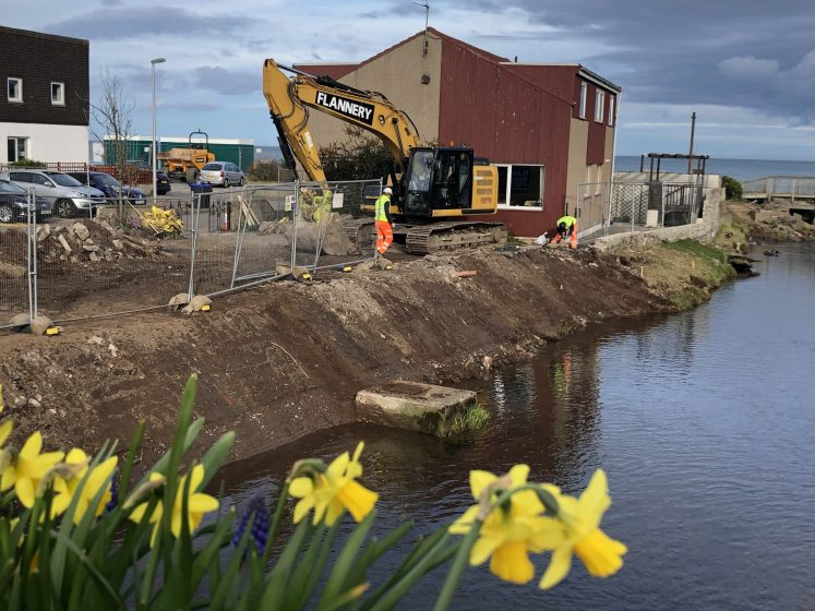 Workmen and machines on riverbanks of Carron