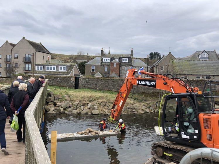 workmen and digger in Carron at pedestrian bridge