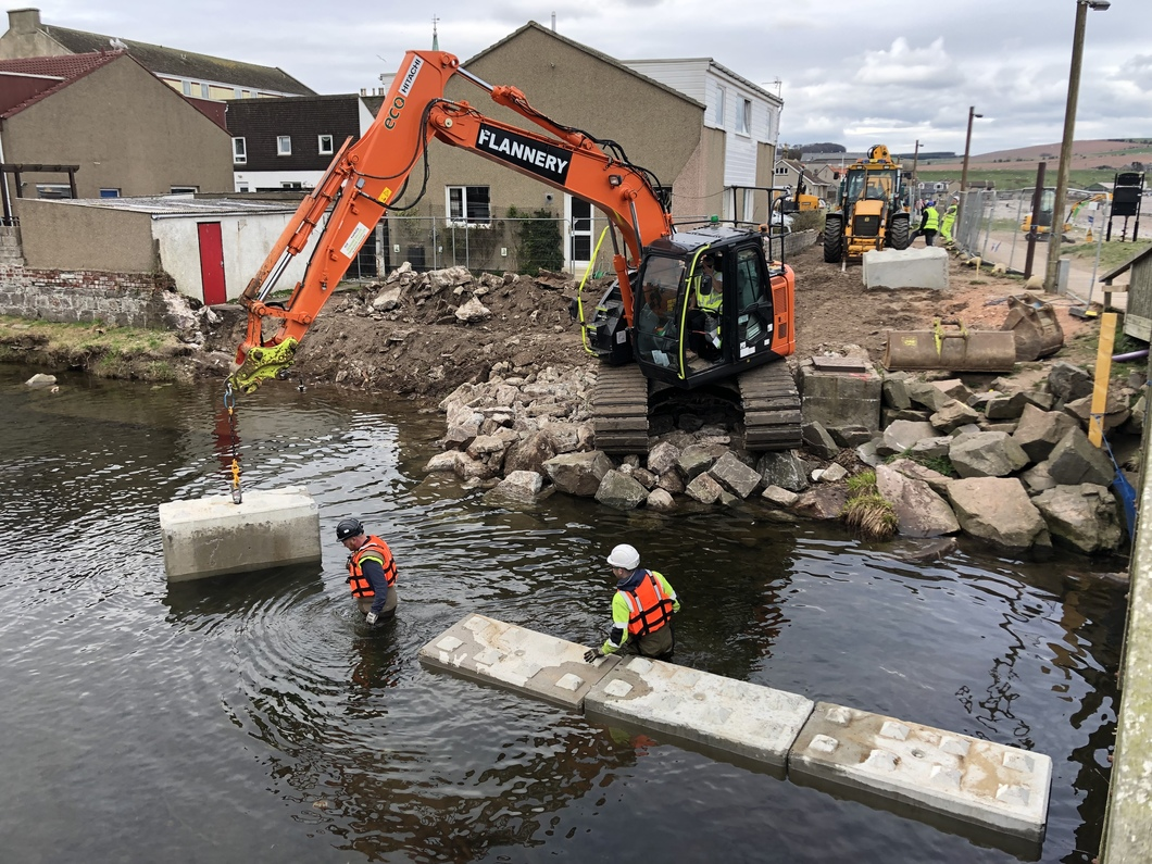 wading workman guide digger as it drops large concrete blocks to form a line down middle of river