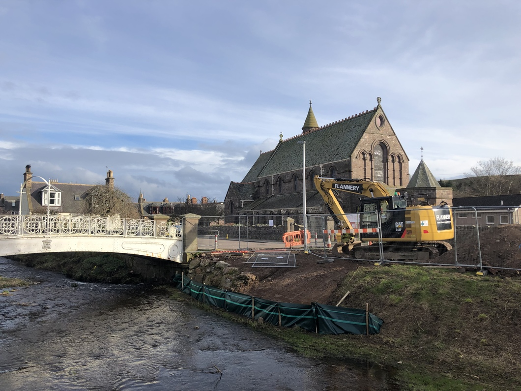 Scene of white bridge and St James Church with  fenced off work area and JCB digger. The river bank has had an access slope scraped into its side