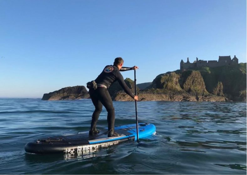 stand up paddle boarder on way to Dunnottar Castle blue sky, calm seas