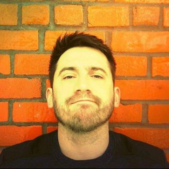 Portrait of Ben in front of brick wall