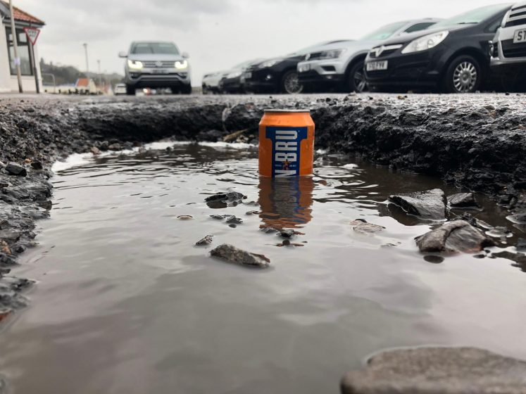 deep pothole with Irn Bru can half submerged in water. beach toilets in background