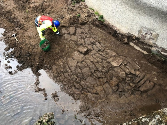 archaeologist examining exposed revetement behind Carron Chip Shop
