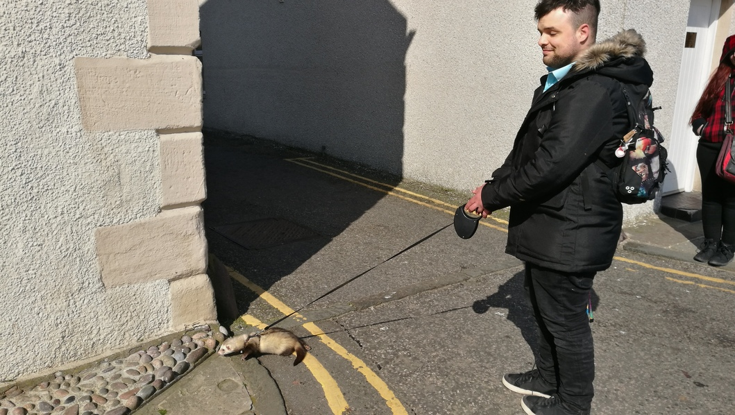 Ally walking with ferret on lead snuffling round corner of building at harbour