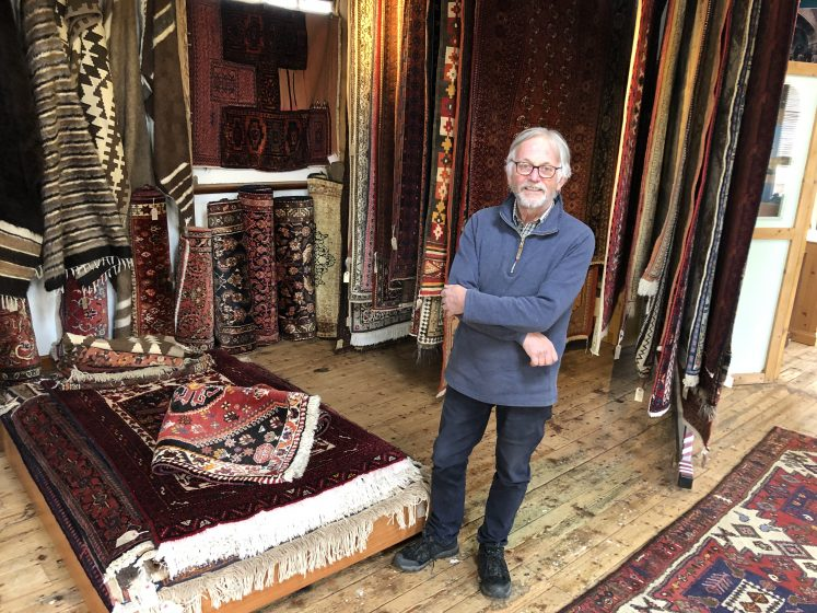 John Briggs standing at back of his shop surrounded by hanging rugs