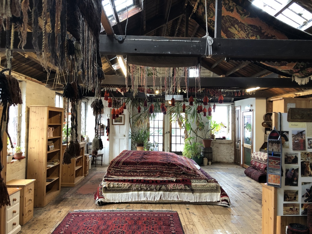 Shot of interior of shop - stack of rugs on floor, ethnic styled furniture pieces also on show