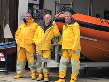 Three lifeboat men dressed in their yellow protective clothing