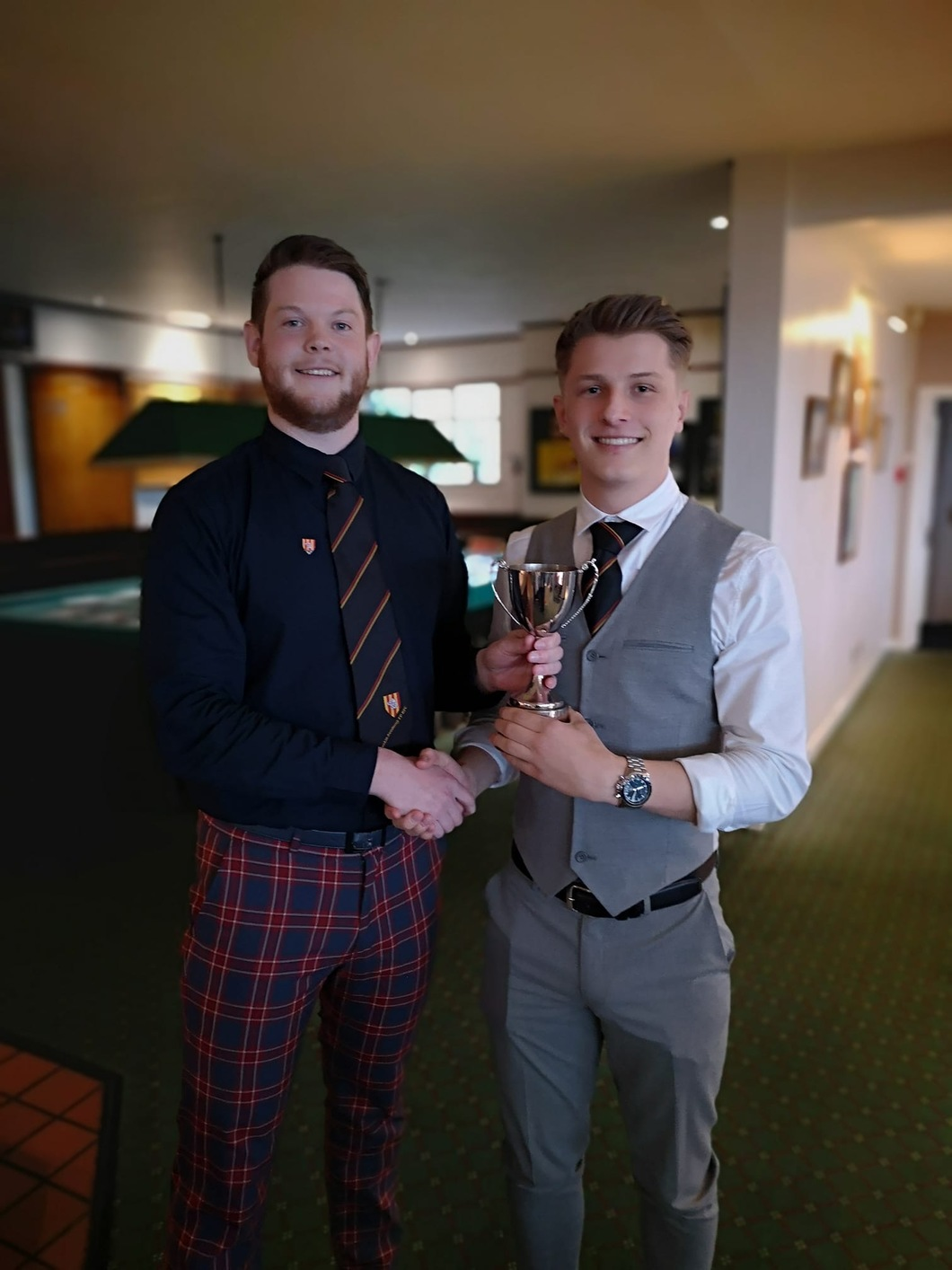 two young men with trophy - one is wearing nice tartan trousers