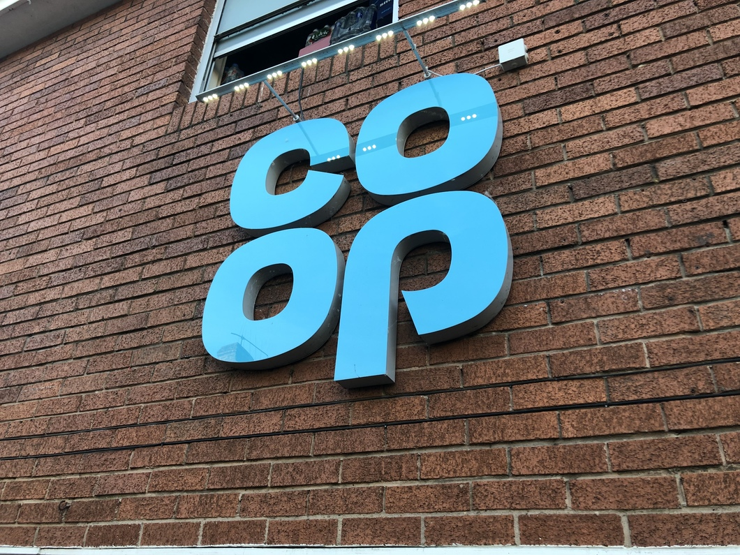 Coop store logo on brick wall