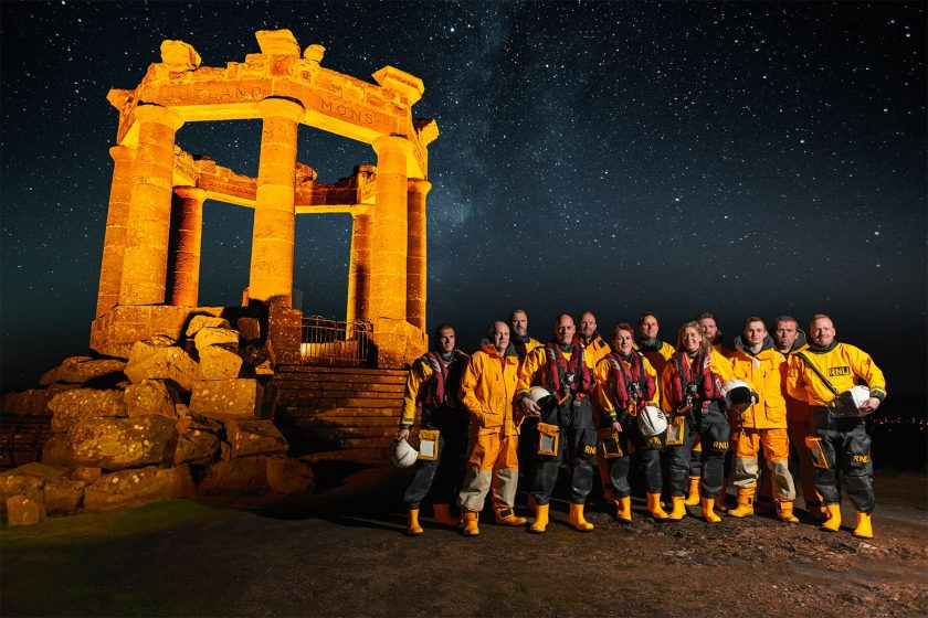 Slightly artful shot of war memorial glowing gold with crew of lifeboat dressed in their yellow weather gear. The sky behind is spangled with stars