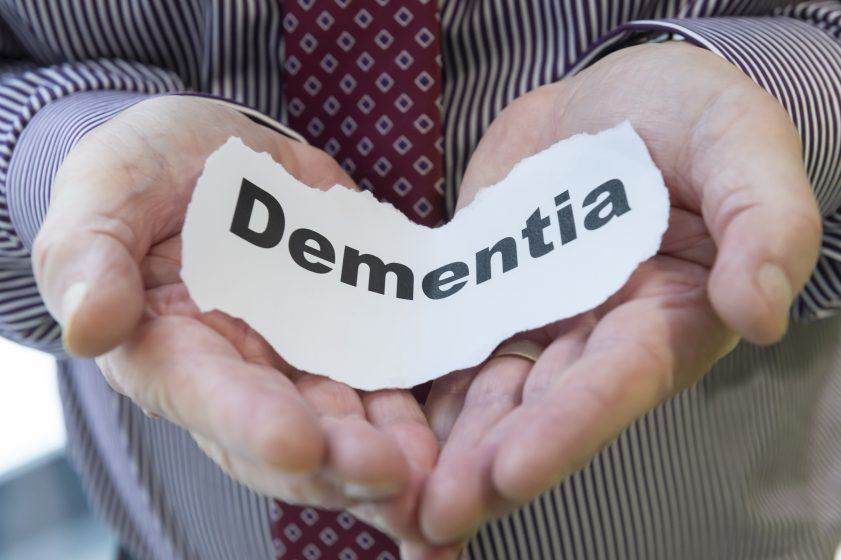 hands cradling piece of paper with word dementia printed on it