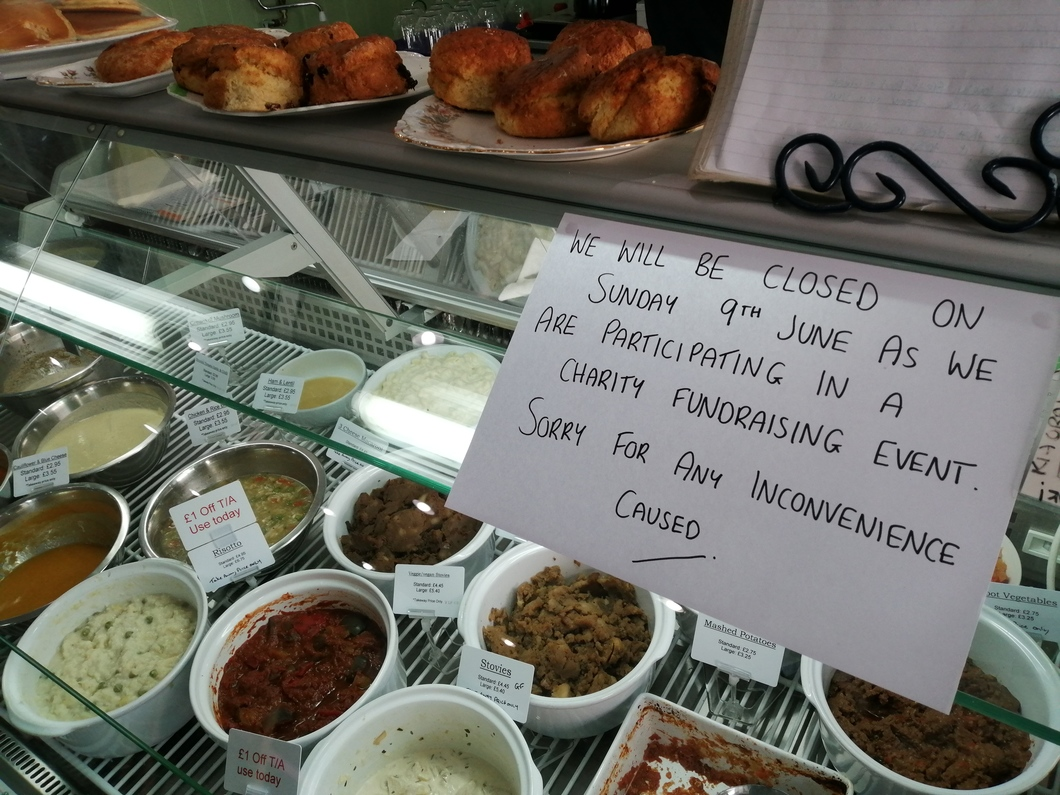 hand written sign on food counter about café closure - scones and food in background
