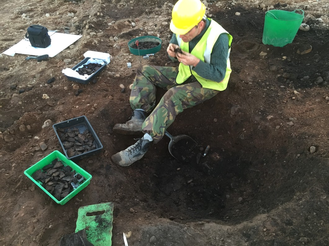 archaeologist in hard hat sitting on ground with trays of pottery fragments