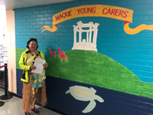 teacher standing beside mural with shows war memorial, stags and a turtle