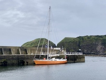 large orange yacht at harbour