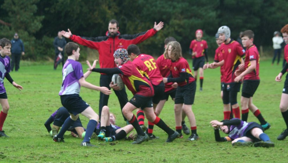 referee with arms wide over scrum of youngsters