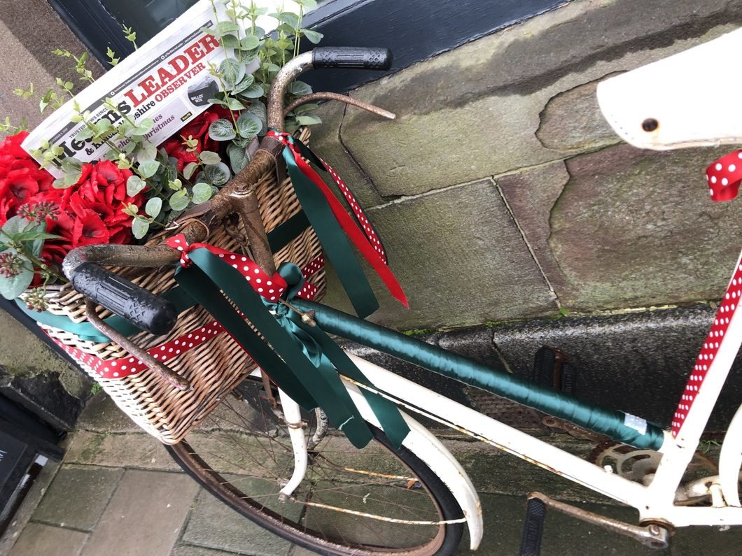 Ladies' bike with basket, flowers and copy of Mearns Leader
