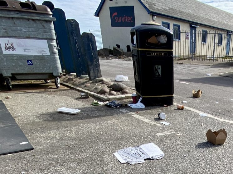 overflowing bin with rubbish on ground